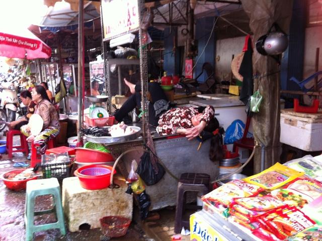 Having a rest at her chicken stall in Vietnam